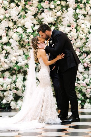detroit-lions-taylor-decker-kisses-wife-bryn-toyama-at-wedding-berta-wedding-gown-flower-wall
