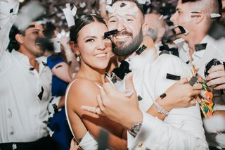 bride-and-groom-smiling-with-confetti-on-dance-floor-at-after-party-reception-diamond-bracelet
