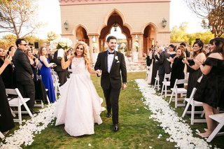 bride-in-pretty-hayley-paige-wedding-dress-holding-grooms-hand-walking-down-grass-aisle-flowers