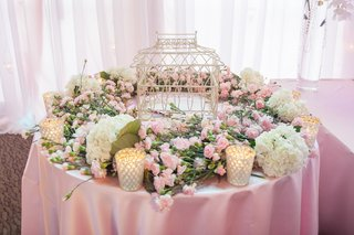 round-table-decorated-with-fresh-flowers-and-birdcage