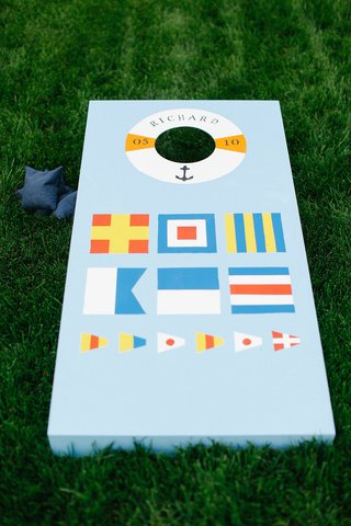 waterfront-wedding-with-nautical-themed-blue-cornhole-board-on-green-lawn