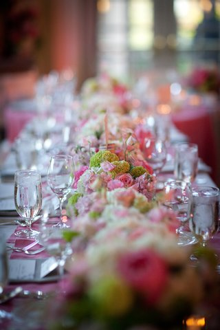 wedding-reception-table-with-a-floral-runner-of-green-and-white-hydrangeas-and-pink-and-white-roses