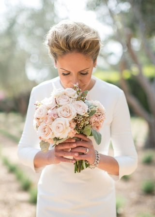 bride-in-three-quarter-sleeve-wedding-dress-smells-rose-wedding-bouquet