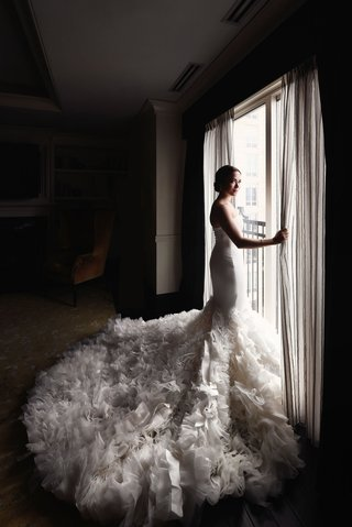 wedding-portrait-bride-looking-out-window-strapless-wedding-dress-mermaid-gown-textured-ruffle-skirt