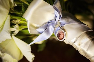 golden-charm-with-rhinestones-around-photo-of-mother-of-the-bride-tied-with-ribbon-to-bridal-bouquet