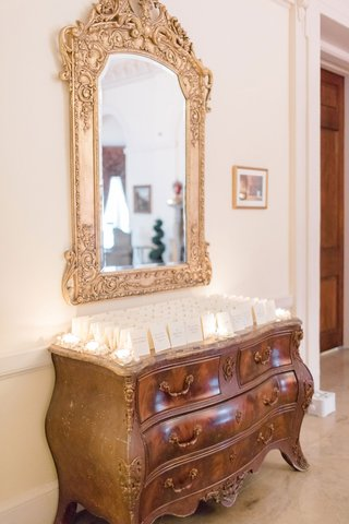 wedding-reception-at-oheka-castle-antique-chest-dresser-with-escort-cards-candlelight-gold-mirror