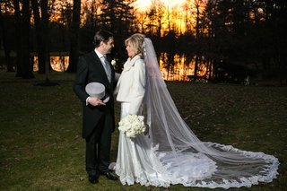 bride-in-a-pnina-tornai-dress-veil-white-fur-coat-white-rose-bouquet-groom-in-morning-coat