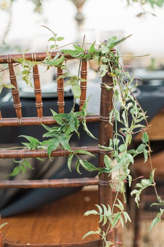 vines-wrapped-around-back-of-wood-chair-rustic-boho-california-reception-wedding-decor