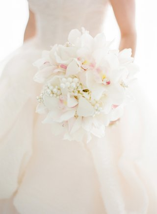 bride-holding-orchids-pearls-and-peonies
