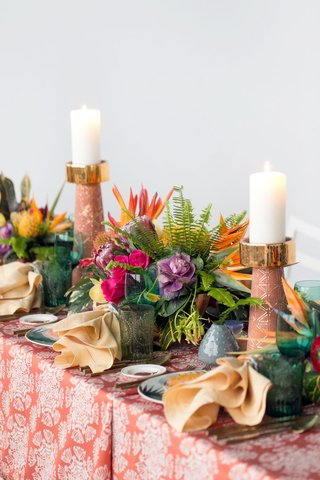 wedding-reception-styled-shoot-green-glassware-tall-candlesticks-orange-pattern-linen-bird