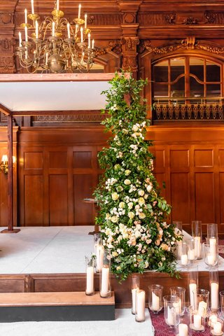 wedding-ceremony-decor-stage-with-pillar-candle-in-hurricane-vases-greenery-arbor-with-white-flowers