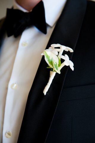 groom-in-tuxedo-wearing-white-stephanotis-boutonniere