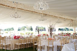 wedding-tent-reception-with-crystal-chandeliers-pink-flower-arrangements-and-golden-chairs