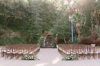 wedding-ceremony-venue-wood-chairs-greenery-white-flowers-outdoor-ceremony-sycamore-and-oak-trees