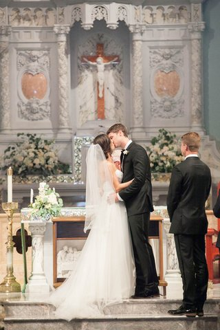 bride-and-groom-kiss-at-the-altar-of-their-catholic-ceremony
