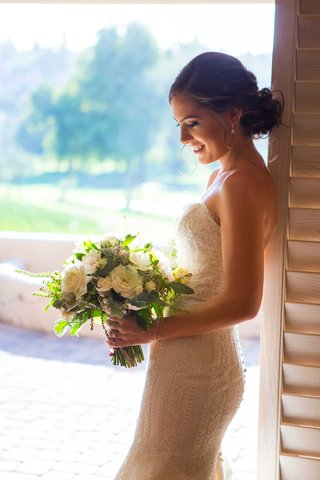 bride-with-low-bun-updo-in-lace-ines-di-santo-gown-smiling-at-bouquet-of-white-and-green