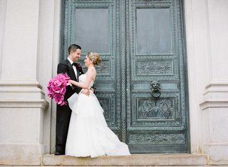 bride-in-reem-acra-wedding-dress-with-pink-orchid-bouquet-and-groom-in-front-of-large-door