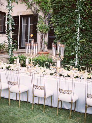 long-tables-white-linens-gold-chairs-white-cushions-low-floral-runner-foliage-gold-candelabra-covers