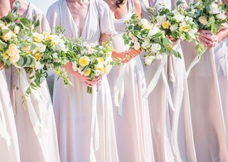 wedding-details-yellow-and-light-pink-flower-bouquets-with-ribbons-for-bridesmaids-neutral-gowns